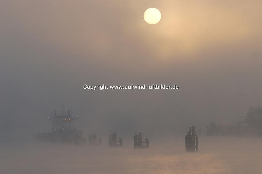 4415/ Reede im Hamburger Hafen: EUROPA, DEUTSCHLAND, HAMBURG,  17.10.2003: ..Schiff auf Reede im Hamburger Hafen in der Norderelbe westlich der Elbbruecken. Nebel und Sonnenaufgang.  .Eine Reede ist ein Ankerplatz vor einem Hafenort oder vor der Mündung einer Wasserstraße...Schiffe warten hier auf die Einfahrt zum Hafen, Kanal oder Fluss. Andere Schiffe werden geleichtert (auf kleine Schiffe umgeladen). ..Das Schiff liegt im Strohm an Duckdalben.