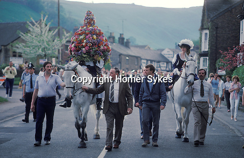 Castleton Garland Day Castleton Derbyshire UK May 29th. Oak Apple Day King and Queen on horseback walk around the village of Castleton. 1980s.