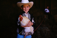 Jeffrey Knox holds a rooster that he snared in the hayloft of his county farm in Gold Beach, Oregon. He and his sister raised chickens and rabbits to show at the Curry County 4-H Fair. County fairs originated in England in the 1600s, when once a year agrarian people gathered to share information. These traditions were continued in rural America but today less than 2 percent of families live on farms.