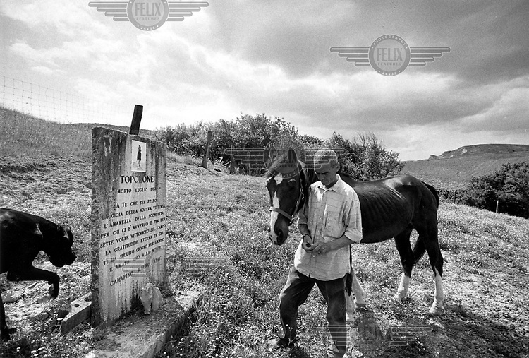 © Francesco Cito / Panos Pictures..Siena, Tuscany, Italy. The Palio. ..'Canapino', a retired jockey who won the Palio a number of times, takes a young horse to visit the grave of Leonardo, one of the most successful horses in the history of the race...Twice each summer, the Piazza del Campo in the medieval Tuscan town of Siena is transformed into a dirt racetrack for Il Palio, the most passionately contested horse race in the world. The race, which lasts just 90 seconds, has become intrinsic to the town's heritage since it was first run in 1597...