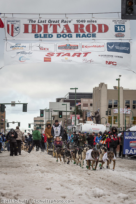 Scott Smith and team leave the ceremonial start line with an Iditarider at 4th Avenue and D street in downtown Anchorage, Alaska during the 2015 Iditarod race. Photo by Jim Kohl/IditarodPhotos.com