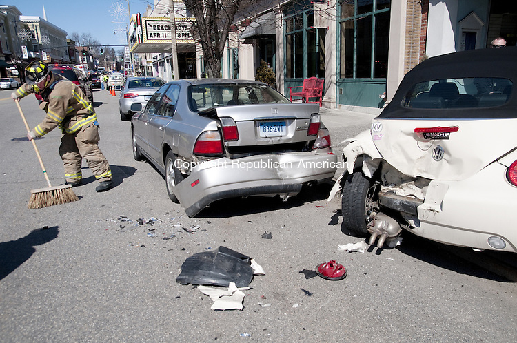 Torrington, CT - 24 March 2014 - 032414AJ03 - A Torrington firefighter cleans up Main Street after a Subaru hit two parked cars Monday afternoon. Alec Johnson/ Republican American