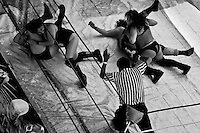 "Female Lucha libre wrestlers pin down their rivals during a fight at a local arena in Mexico City, Mexico, 30 April 2011. Lucha libre, literally ""free fight"" in Spanish, is a unique Mexican sporting event and cultural phenomenon. Based on aerial acrobatics, rapid holds and the use of mysterious masks, Lucha libre features the wrestlers as fictional characters (Good vs. Evil). Women wrestlers, known as luchadoras, often wear bright shiny leotards, black pantyhose or other provocative costumes. Given the popularity of Lucha libre in Mexico, many wrestlers have reached the cult status, showing up in movies or TV shows. However, almost all female fighters are amateur part-time wrestlers or housewives. Passing through the dirty remote areas in the peripheries, listening to the obscene screams from the mainly male audience, these no-name luchadoras fight straight on the street and charge about 10 US dollars for a show. Still, most of the young luchadoras train hard and wrestle virtually anywhere dreaming to escape from the poverty and to become a star worshipped by the modern Mexican society."