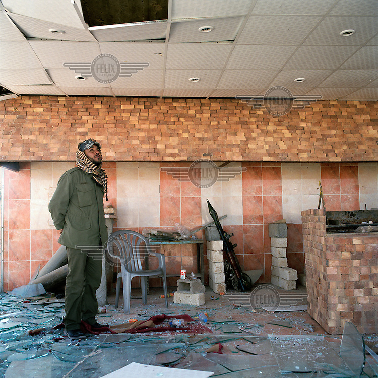 A rebel surveys the damage to a shop after Gaddafi forces were driven from Ajdabiya. On 17 February 2011 Libya saw the beginnings of a revolution against the 41 year regime of Col Muammar Gaddafi.