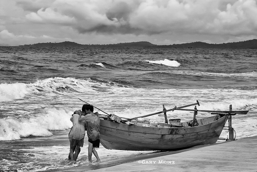 Three fishermen on Phu Quoc Island, Vietnam fight the waves to launch their boat.