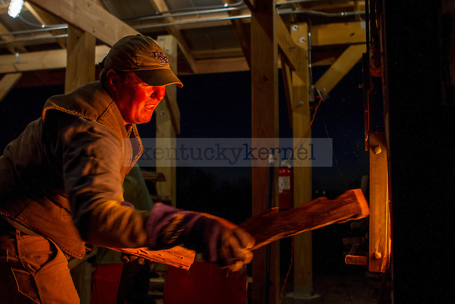 Ceramics Professor Hunter Stamps inches his way toward the door in the kiln. The heat emanating from the kiln makes him squint. Wood was fed into the kiln at all hours of the day and night so that it reached temperatures in excess of 2100°F.   in Lexington, Ky., on Saturday, November, 17, 2012. Photo by James Holt | Staff