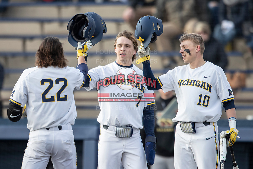 Michigan Wolverines Jesse Franklin (7) and Blake Nelson (10) greet Jordan Brewer (22) after his home run against the Western Michigan Broncos on March 18, 2019 in the NCAA baseball game at Ray Fisher Stadium in Ann Arbor, Michigan. Michigan defeated Western Michigan 12-5. (Andrew Woolley/Four Seam Images)
