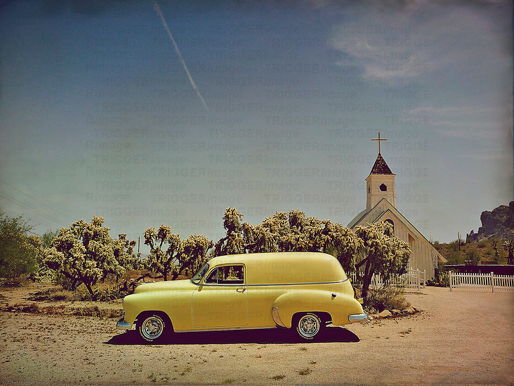 A yellow pickup in USA desert location with church