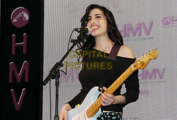 "AMY WINEHOUSE.At HMV Oxford Circus Promoting Her New Album ""Take The Box"".15 January 2004.guitar, half length, half-length, smiling, stage .www.capitalpictures.com.sales@capitalpictures.com.©Capital Pictures"