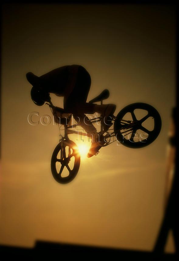 silhouette of a stunt bike rider