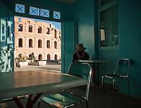 Man sitting in cafe bar overlooking Roman amphitheatre, El Djem, Tunisia
