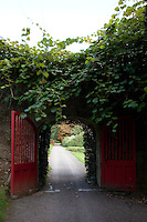 Double gates open an archway into the flower garden