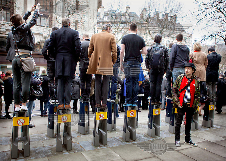 People wtaching the funeral procession of Margret Thatcher stand on bicycle racks in order to get a vantage point. Margaret Thatcher, the former British Prime Minister, died on 8 April 2013 after suffering a stroke. She was accorded the rare accolade of a ceremonial funeral.
