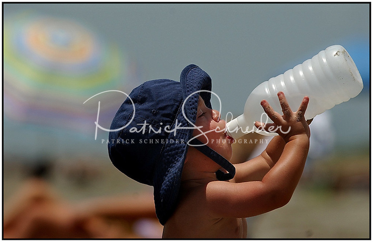 A child drinks from a water bottle to stay hydrated at the beach. Photo taken on Sullivan's Island, near Charleston, SC.  Model released image.