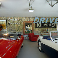 Malcolm McDowell's collection of sports cars is housed in a separate building decorated with vintage posters