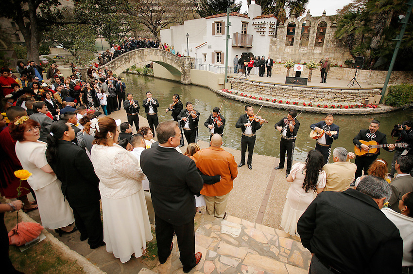 """""""We do!"""" said 400 couples on San Antonio's romantic River Walk during Valentine's Day mass weddings. This annual exchange of love draws couples from across the nation to one of the country's most passionate cities. Here, mariachis perform romantic serenades on the bank of the meandering San Antonio River. (Darren Abate/pressphotointl.com)"""