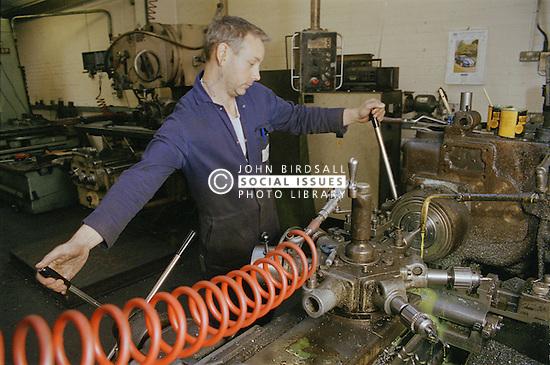 Man centre lathe turning at engineering works,