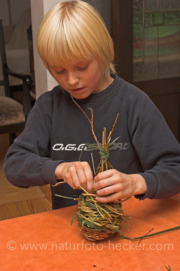 Kinder flechten Nistkugel für Vögel, Vogel, Nisthilfe, Nest, Kugelnest. Junge, Kind verflechtet dünne Zweige