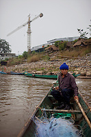 "Mon, 62, has been a fisherman for 10 years on the Mekong River in Sop Ruak, Thailand. He says things were better before China built dams and controlled the water level of the river. ""I used to cast my net and catch 10-12 fish now I some times come back with none,"" he said. Photo taken on Thursday, December 10, 2009. Kevin German / Luceo Images"