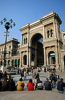 People sitting on the Piazza Del Duomo admiring the view of the Galleria Vittorio Emanuele II, Milan, Italy.