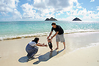 A family of three playing on Waimanalo Beach, O'ahu, with the Mokulua Islands in the distance.
