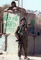 An Israeli soldier stops Palestinians from approaching the IDF Checkpoint near the West Bank town of Ramallah May 29, 2002. Israeli security forces tighten all the entrances to Jerusalem and exits from the West Bank due the high alert on possible suicides attacks. Photo by Quique Kierszenbaum