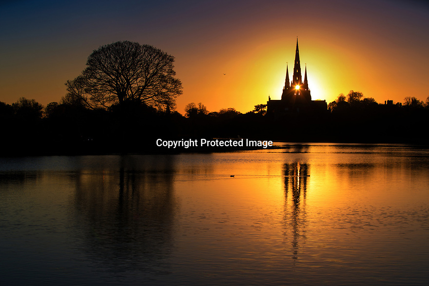 02/11/18<br /> <br /> Ahead of a cold night the setting sun shines through the central spire of Lichfield Cathedral, and is reflected in Stowe Pool.<br /> <br /> The Staffordshire medieval cathedral  is the only English cathedral with three spires. The three spires are often referred to as 'the Ladies of the Vale'.<br /> <br /> <br /> <br /> <br /> All Rights Reserved, F Stop Press Ltd. (0)1335 344240 +44 (0)7765 242650  www.fstoppress.com rod@fstoppress.com