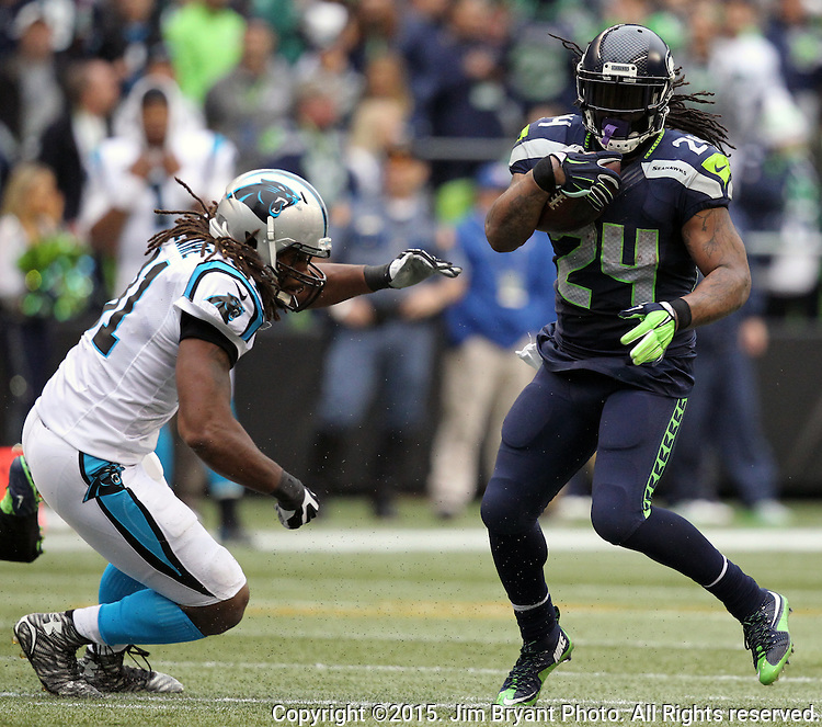 Seattle Seahawks  running back Marshawn Lynch (24) slips by Carolina Panthers defensive end Ryan Delaire (91) at CenturyLink Field in Seattle on October 18, 2015. The Panthers came from behind with 32 seconds remaining in the 4th Quarter to beat the Seahawks 27-23.  ©2015 Jim Bryant Photography. All Rights Reserved.