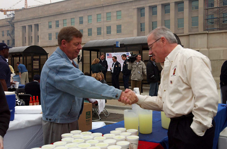 """6Isakson112701 -- John Isakson, R-Ga., greets Bob Barr, R-Ga., during the Pentagon Renovation Program  """"Southern Cookout"""" to salute the men and women who assisted in the recovery effort and are working still to rebuild the Pentagon. The """"Southern Salute"""" cookout was put on by Williamson Bros. Bar-B-Q of Marietta, Ga."""