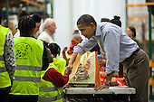 United States President Obama hands out food to the needy for Thanksgiving at the Capital Area Food Bank in Washington DC, USA, 21 November 2012..Credit: Jim LoScalzo / Pool via CNP