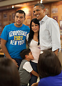 United States President Barack Obama poses for a picture with an unidentified family as he and first lady Michelle Obama greet members of the U.S. military and their families as they eat a Christmas Day meal at Anderson Hall mess hall at Marine Corps Base Hawaii on Sunday, December 25, 2011 in Kaneohe, Hawaii.  .Credit: Kent Nishimura / Pool via CNP
