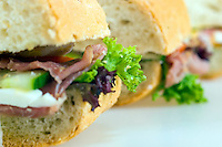 Close up of small sandwiches contains ham and vegetables. A peace of green salad is in the focus