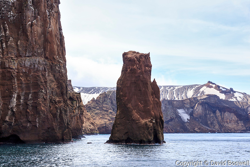 A rock pillar stands watch in Neptune's Bellows, the entrance to Port Foster, the large body of water created by the volcanic caldera that forms Deception Island, in the South Shetland Islands near the Antarctic Peninsula.