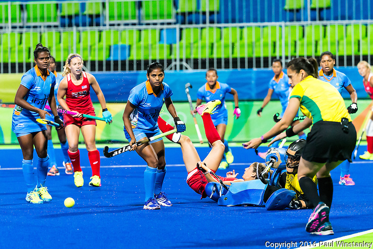 Katie Reinprecht #14 of United States takes a tumble as the ball is cleared by the goalkeeper during the USA vs India women's Pool B game at the Rio 2016 Olympics at the Olympic Hockey Centre in Rio de Janeiro, Brazil.