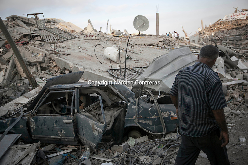 "In this Friday, Aug. 15, 2014 photo, a Palestinian man walks by the rubble of house buildings destroyed by israeli airstrikes during the ""Protective Edge"" military operation in Shuyaja neighborhood in Gaza City. After a five days truce was declared on 13th August between Hamas and Israel, civilian population went back to what remains from their houses and goods in Gaza Strip. (Photo/Narciso Contreras)"
