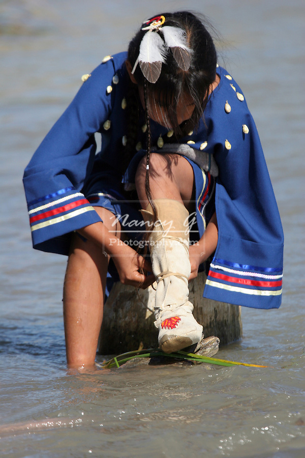 A young Native American Indian girl sits on a log in the river putting on her moccasins