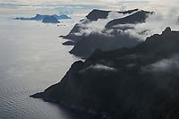 Mountain peaks emerge from the clouds in the west of Moskenesøy, Lofoten Islands, Norway