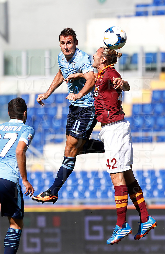 Calcio, Serie A: Roma vs Lazio. Roma, stadio Olimpico, 22 settembre 2013.<br /> Lazio forward Miroslav Klose, of Germany, and AS Roma defender Federico Balzaretti , right, jump for the ball during the Italian Serie A football match between AS Roma and Lazio, at Rome's Olympic stadium, 22 September 2013.<br /> UPDATE IMAGES PRESS/Isabella Bonotto