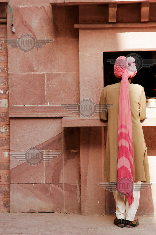 A man in a turban standing outside a shop.