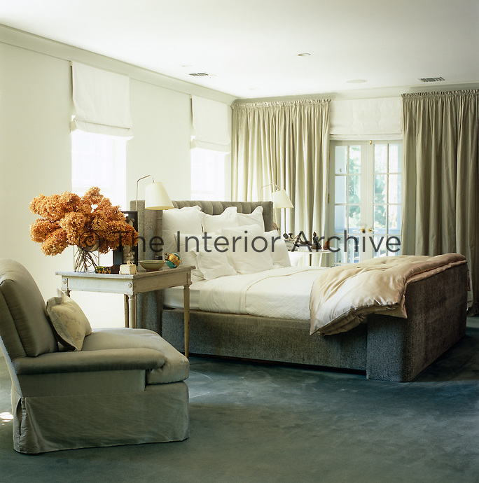 In this elegant and comfortable bedroom the bed, carpet, armchair and curtains are all in toning shades of grey