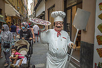 Italy. Liguria Region. San Remo. Street in the town center. The statue of a pizzaiolo carrying a big delicious pizza. A group of muslim women wearing masks to protect themselves from the Coronavirus (also called Covid-19). The safety sanitary measures advocate people to stand apart in order to avoid close contact and potential contamination by coronavirus. Liguria is a region of north-western Italy. Sanremo or San Remo is a city and comune in the Province of Imperia. 28.07.2020 © 2020 Didier Ruef