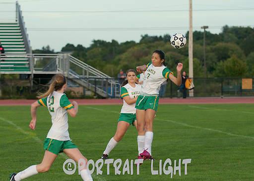 CHS senior Sarah Nobrega (right) heads the ball, while freshman Maddy LaBree looks on.