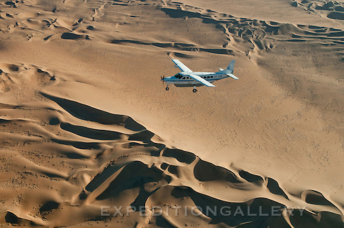 Small airplane (Cessna Caravan) flying low over dunes of the Namib Desert while flightseeing, Namib-Naukluft National Park, Namibia. [NO PROPERTY RELEASE]