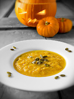 Pumpkin & Bacon Soup with a traditional Haloween pumpkin with a carved face