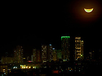 Manila, Philippines Large crest moon, half moon over buildings in Manila, Philippines