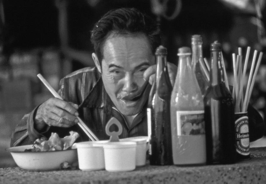 Lao worker eats at outdoor Vientiane restaurant