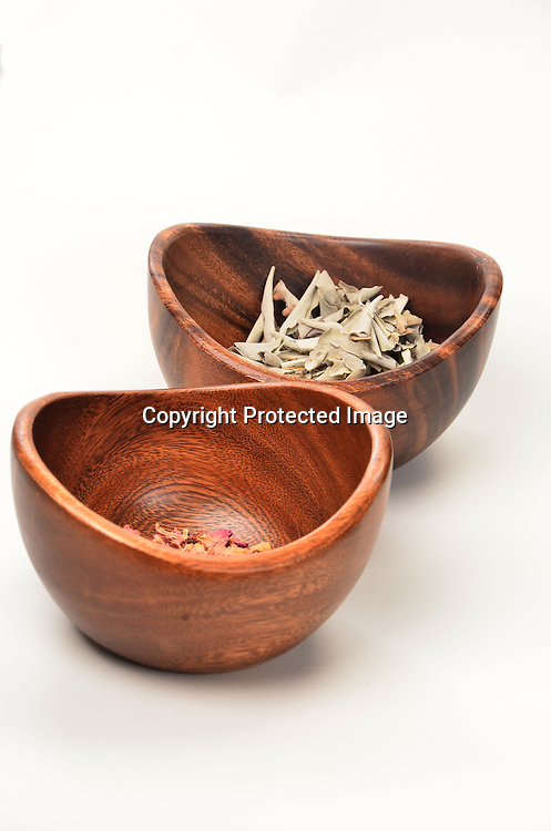 Stock photo of rose petals and eucalyptus herbs in a wooden bowl
