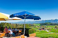 Deutschland, Bayern, Oberbayern, Chiemgau, Rimsting: Terrasse des Berggasthofs und Hotels Weingarten auf der Ratzinger Hoehe mit wunderschoenem Ausblick ueber das Bayerische Voralpenland und den Chiemsee bis in die Chiemgauer Alpen | Germany, Upper Bavaria, Chiemgau, Rimsting: terrace of Inn and Hotel Weingarten at Ratzinger Hoehe with view across the Bavarian Alpine Uplands with Lake Chiemsee and the Chiemgau Alps