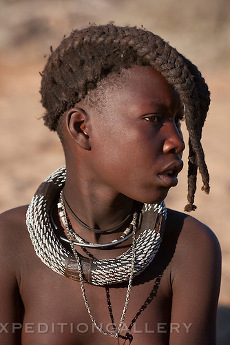 A young Himba girl with necklaces wearing her hair braided forward over her face in a style traditional for girls prior to reaching puberty. Himba are nomadic herders of goats and cattle, living in the dry desert regions of northwestern Namibia and southern Angola. [NO MODEL RELEASE]
