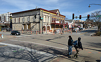 NWA Democrat-Gazette/ANDY SHUPE<br /> Pedestrians cross Dickson Street Wednesday, Nov. 27, 2019, at West Avenue as work to renovate the former Hog Haus Brewery building continues in downtown Fayetteville. The city has held discussions about creating some kind of a downtown association that would oversee maintenance and activities at the cultural arts corridor once it's built. Downtown associations can serve a variety of functions, including pursuing grants and raising money toward revitalization projects.
